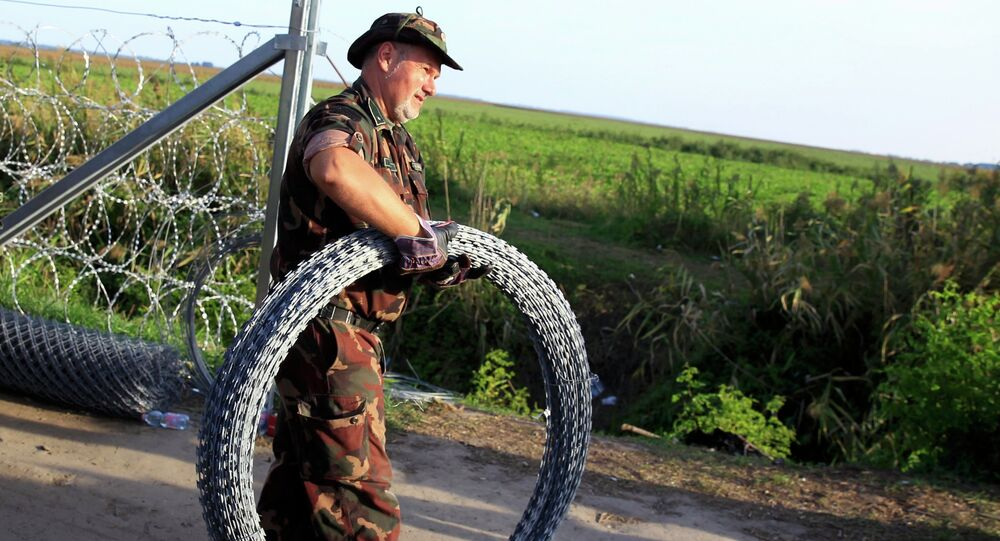 Hungarian soldier carries barbed wire for a fence under construction along the border with Serbia near the migrant collection point in Roszke, Hungary, September 14, 2015