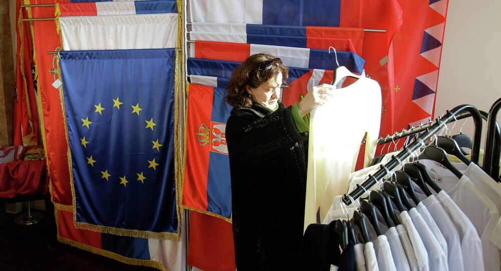 In this photo taken Wednesday, Dec. 7, 2011, a woman looks at an item of clothing in a shop as she stands next to a European Union flag and Serbian flags, in Belgrade, Serbia