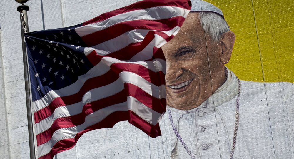 The US flag flies in front of a mural of Pope Francis on the side of a building in midtown Manhattan in New York August 28, 2015
