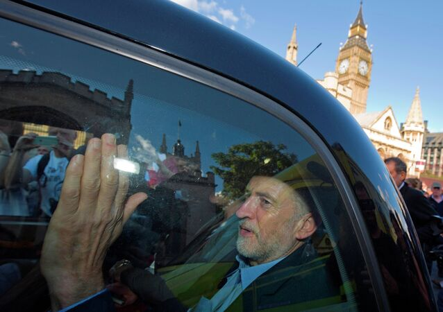 Newly elected leader of Britain's opposition Labour party, Jeremy Corbyn, passes the Houses of Parliament and Big Ben as he leaves in the back of a taxi after addressing a pro-refugee rally in central London on September 12, 2015.