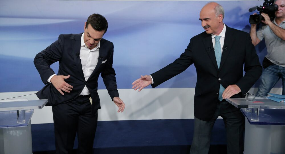 Former Greek Prime Minister Alexis Tsipras, left, and the leader of the left-wing Syriza party, is blocked by microphone wiring as he tries to approach main opposition conservative New Democracy head Vangelis Meimarakis, right, to shake hands prior to a live televised debate at the state-run ERT television in Athens, Monday, Sept. 14, 2015. Greece is holding a snap general election on Sept. 20, 2015.