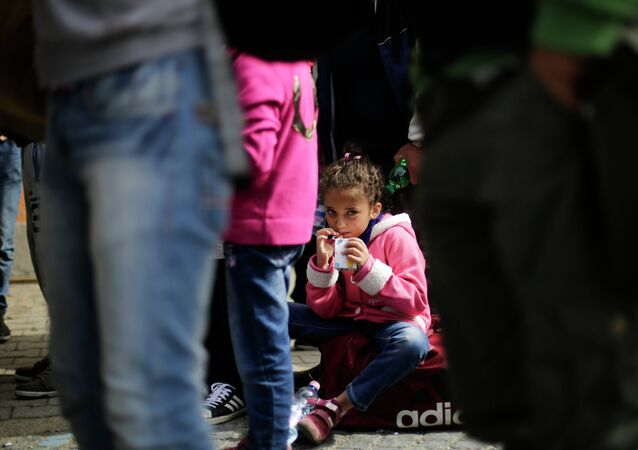 A girl drinks some juice after she arrived with other refugees at the train station of the southern German border town Passau, Tuesday, Sept. 15, 2015.