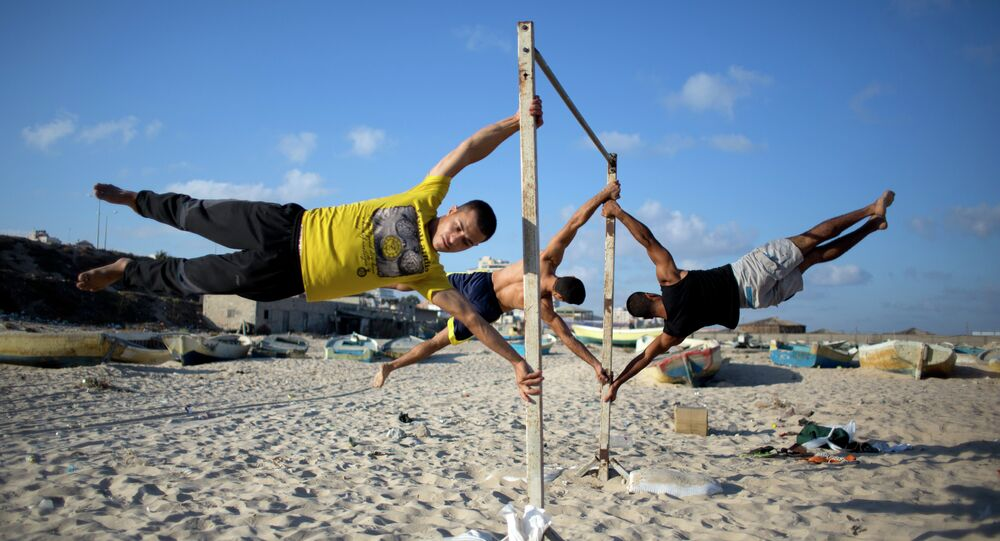 Members of Bar Palestine, a street workout team practice their skills during a training session on the beach of Gaza City