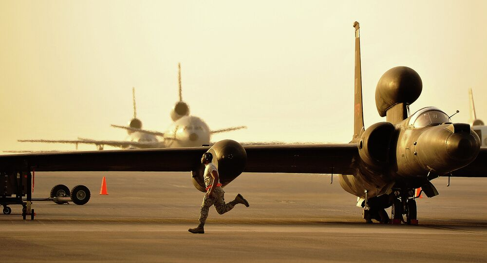 A member of the 380th Expeditionary Aircraft Maintenance Squadron assists in the removal of the temporary landing gear on a U-2.