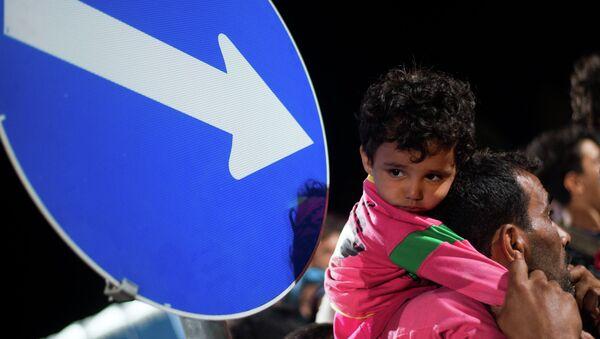 Refugees queue up for a bus, as they arrive at the border between Austria and Hungary, Heiligenkreuz, Austria, late Tuesday Sept. 15, 2015. - Sputnik International