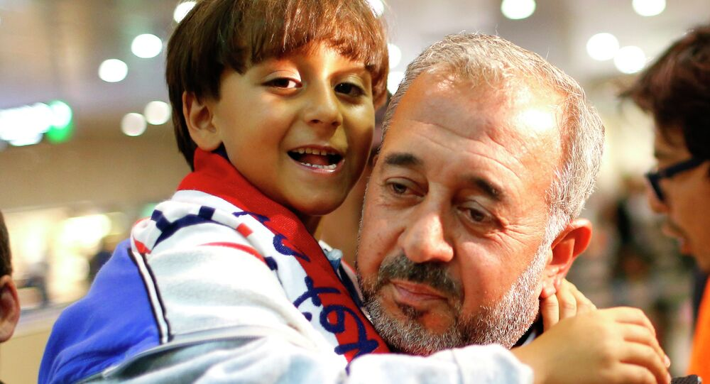 Syrian Osama Abdul Mohsen holds his son Zaid as they arrive at the Barcelona train station on September 16.
