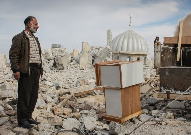 Syrian man salvages furniture from his home that was destroyed in bombing, in the northwestern city of Maraat al-Numan, Syria