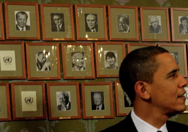 President Barack Obama sits in front of framed photos of previous Nobel Peace Prize winners during a Signing Ceremony at the Norwegian Nobel Institute in Oslo, Norway, Thursday, Dec. 10, 2009.