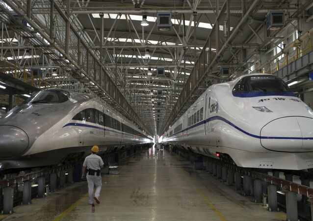 A worker walks between two bullet trains at a high speed railway maintenance station.