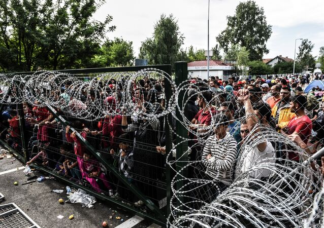 Refugees stand behind a fence at the Hungarian border with Serbia near the town of Horgos on September 16, 2015