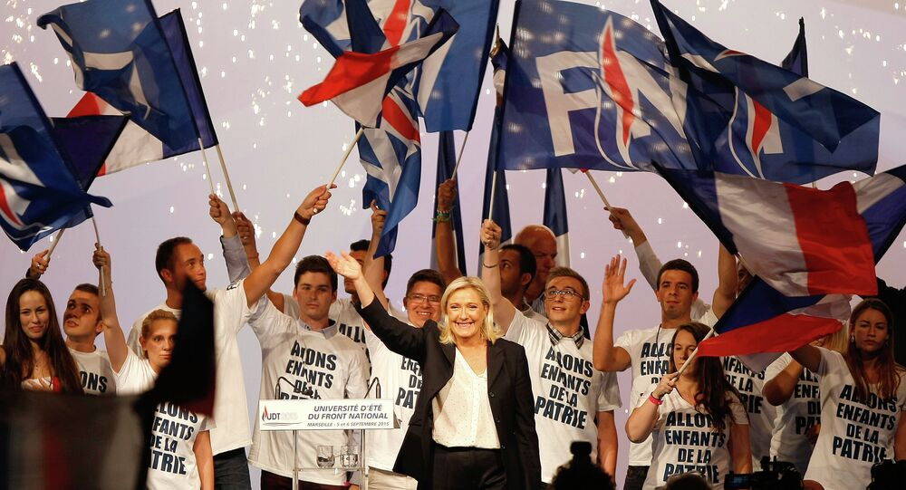 France's far-right National Front president Marine Le Pen, center, surrounded by members, waves to supporters after her speech during their meeting in Marseille, southern France, Saturday, Sep. 6, 2015.