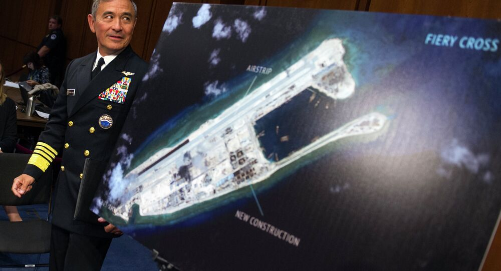 Adm. Harry B. Harris, Jr., US Navy Commander, U.S. Pacific Command walks past a photograph showing an island that China is building on the Fiery Cross Reef in the South China Sea