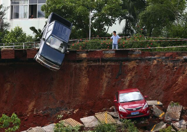 A man looks on as cars are seen stuck in a sinkhole that occurred in a parking area after heavy rainfall hit Haikou, Hainan province, China