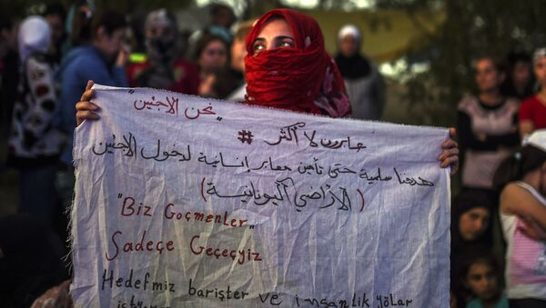 A Syrian woman stands holding a banner that reads in Turkish ''we are migrants, we will pass'' and in Arabic (top),  We are only crossing, our aim is peaceful to secure humanitarian passage allowing refugees to enter Greece  near the highway, on their way to the border between Turkey and Greece - Sputnik International