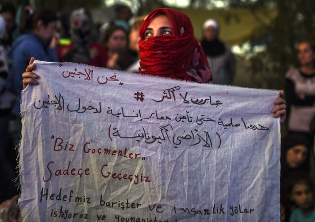 A Syrian woman stands holding a banner that reads in Turkish ''we are migrants, we will pass'' and in Arabic (top),  We are only crossing, our aim is peaceful to secure humanitarian passage allowing refugees to enter Greece  near the highway, on their way to the border between Turkey and Greece