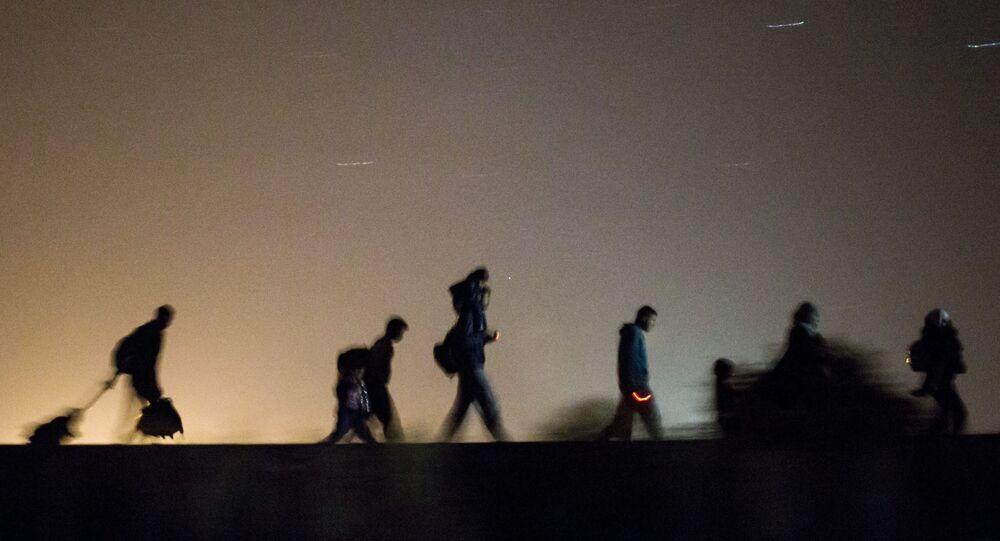 Migrants walk towards a checkpoint along the railway tracks connecting Horgos and Szeged near Roszke, in the vicinity of the border between Hungary and Serbia