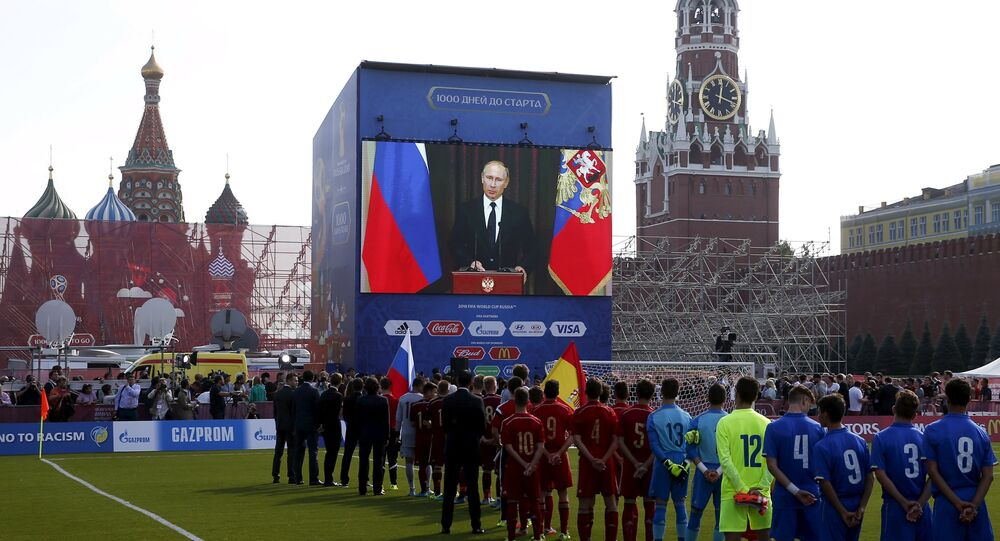 Officials, participants of a soccer exhibition under-16 tournament and spectators listen to Russia's President Vladimir Putin delivering a speech via a video link from Sochi, during a ceremony marking 1,000 days until the beginning of the 2018 FIFA World Cup in Red Square in central Moscow, Russia, September 18, 2015