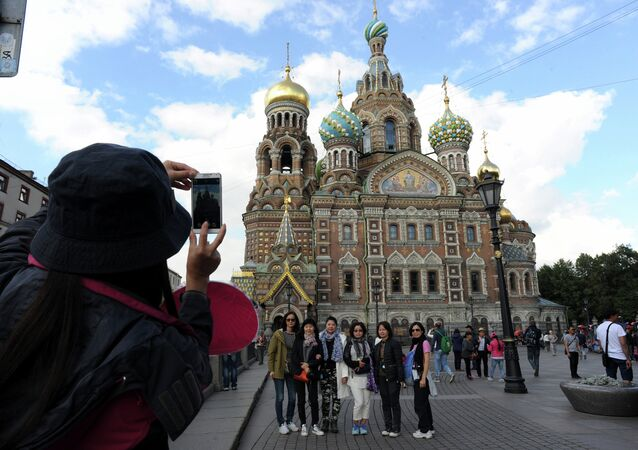 A picture taken on September 4, 2015 shows Chinese tourists as they have their photo taken in front of Church of the Savior on Blood  in central St. Petersburg. Drawn by its Communist past and a visa-free regime, Chinese tourists are flocking to Russia in droves as it develops new routes touting red tourism