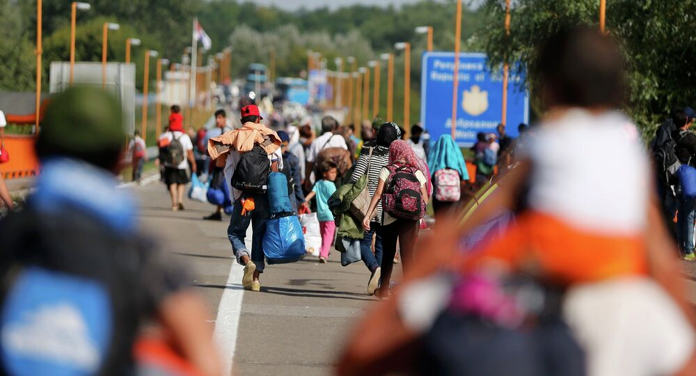 Migrants walk back to Serbia after Croatia refused them entry on the border bridge in Batina, Croatia September 18, 2015.