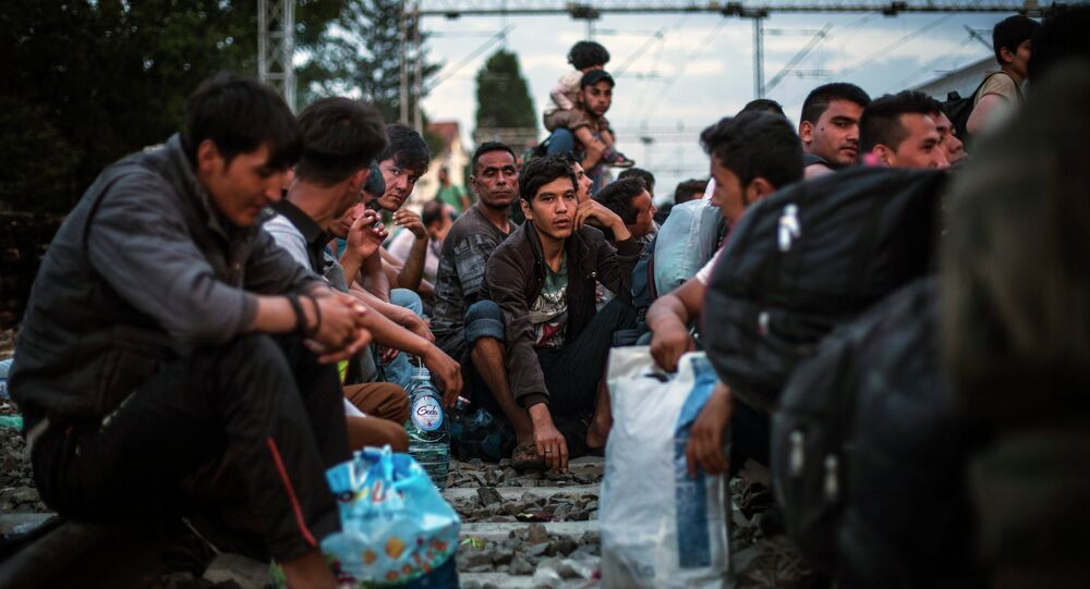 Migrants wait to be allowed by Croatian police to board a train at the station in Tovarnik, Croatia, Saturday, Sept. 19, 2015