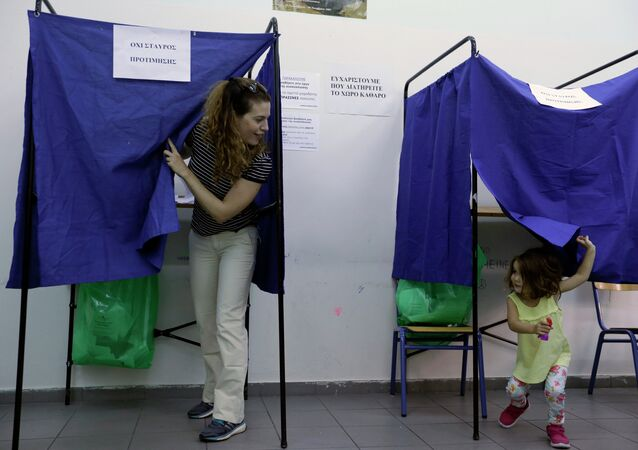 A woman casts her vote as her three-year old daughter plays in an election booth at a polling station in Athens, Sunday, Sept. 20, 2015
