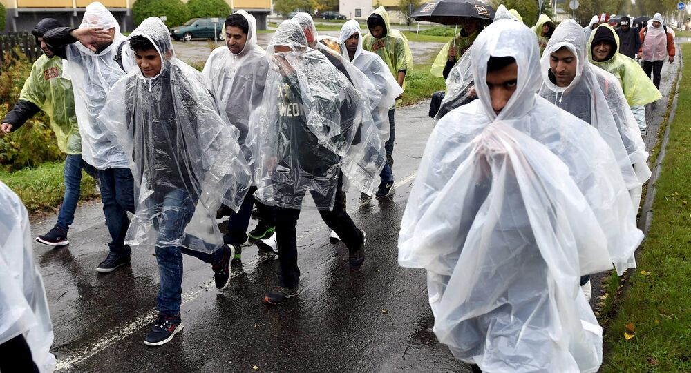 Refugees walked in heavy rain from a public transport centre to Lappia-building refugee reception centre in Tornio, northwestern Finland, September 18, 2015