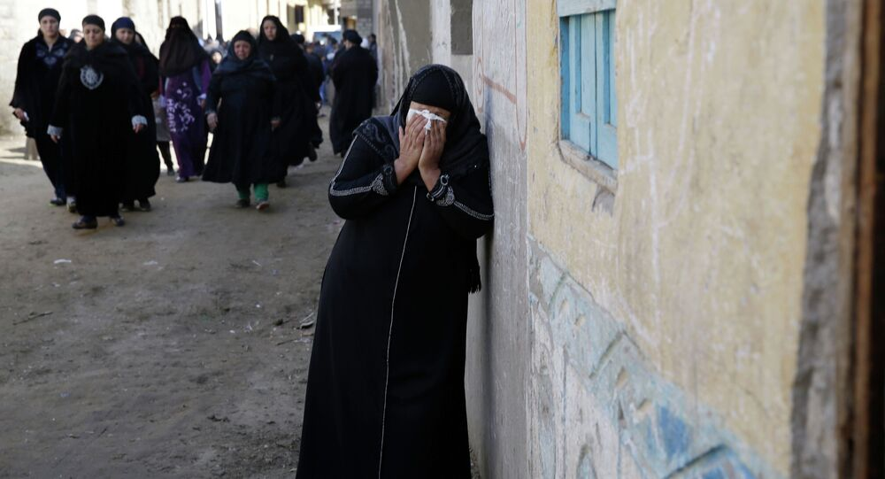 A woman mourns for the Egyptian Coptic Christians captured in Libya and killed by militants affiliated with the Islamic State group, outside of the Virgin Mary church in the village of el-Aour, near Minya, 220 kilometers (135 miles) south of Cairo, Egypt, Monday, Feb. 16, 2015