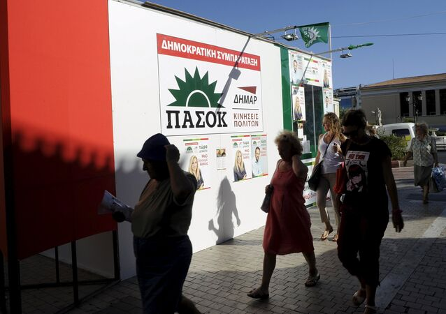 People walk in front of a pre-election kiosk of the Greek Socialist party PASOK in Athens, Greece, September 17, 2015