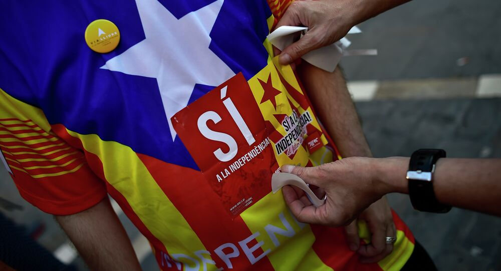 A pro-independence Basque puts a sticker on a T-shirt which reads, ''Yes for the Independence'', during a march to support the pro-independence Catalonia movement, in Pamplona, northern Spain.