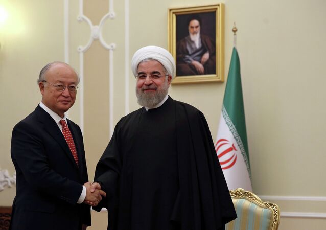 Iranian President Hassan Rouhani, center, welcomes U.N. nuclear chief Yukiya Amano at the start of their meeting in Tehran, Iran, Sunday, Sept. 20, 2015