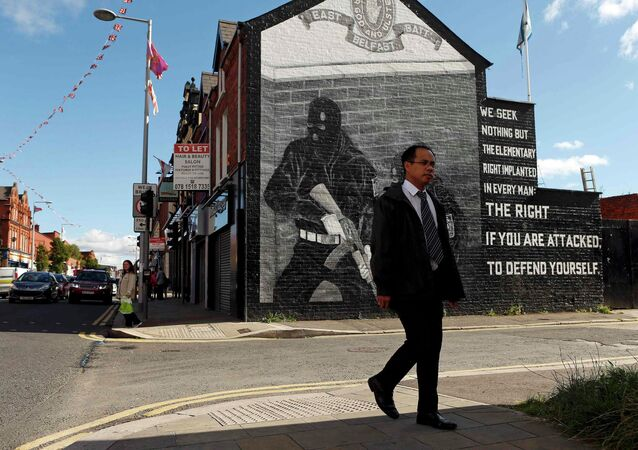A man walks past a mural in East Belfast in Northern Ireland, September 18, 2015
