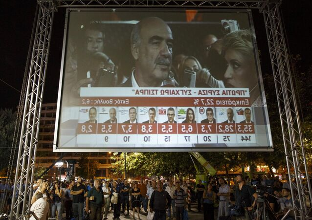 People look at the results of exit polls on a giant screen as the leader of the conservative New Democracy party Vangelis Meimarakis is interviewed on television after polls closed in a general election in Athens, Greece, September 20, 2015
