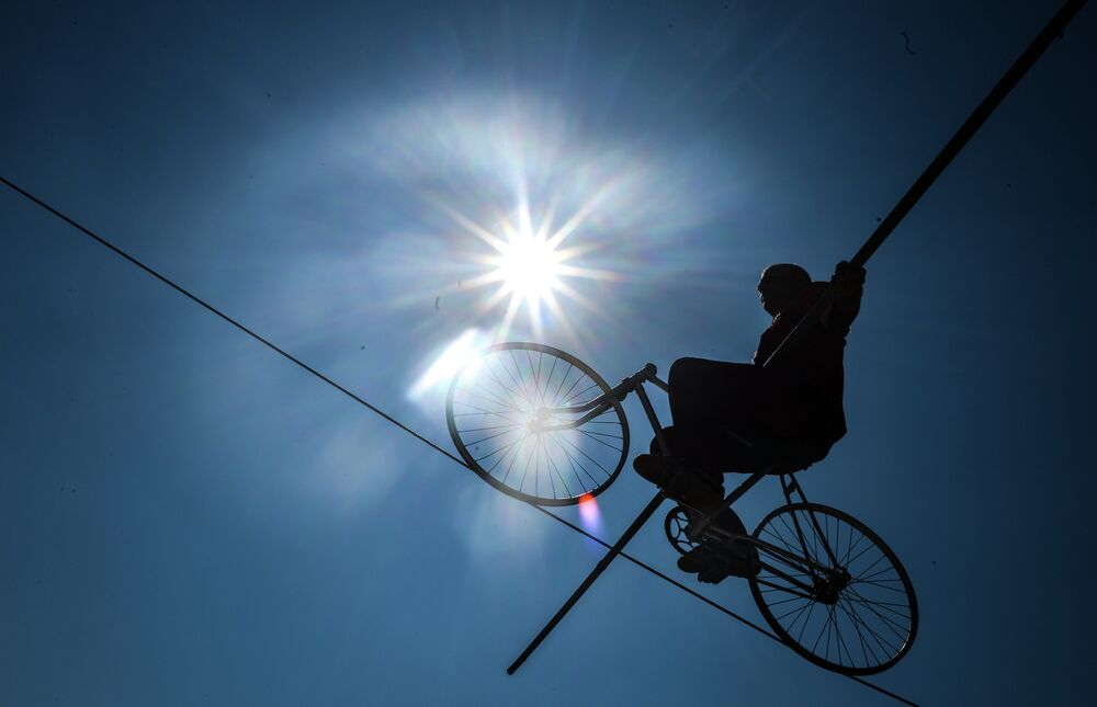 A man on a bicycle offering guests a daring highwire performance on Freedom Square.