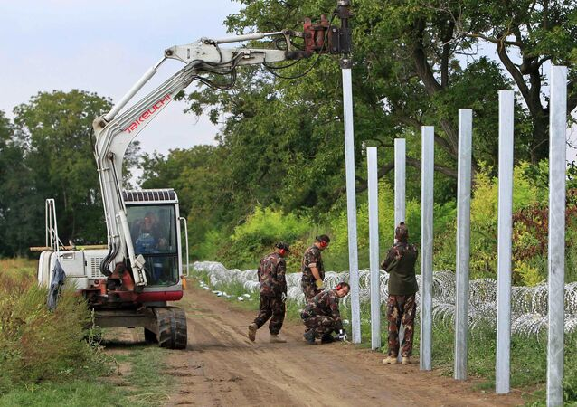 Soldiers build a barbed wire fence at the Hungary-Croatia border near Sarok, Hungary, September 20, 2015.