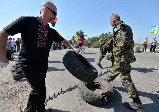 Militants and servicemen block the road with tyres at the checkpoint between Ukraine and Crimea, in Chongar, on September 20, 2015