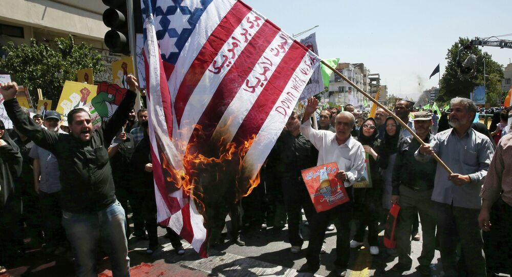 Iranian demonstrators burn a representation of the U.S. flag reading down with America, in Arabic and Persian, during an annual pro-Palestinian rally marking Al-Quds (Jerusalem) Day at the Enqelab-e-Eslami (Islamic Revolution) St. in Tehran, Iran, Friday, July 10, 2015