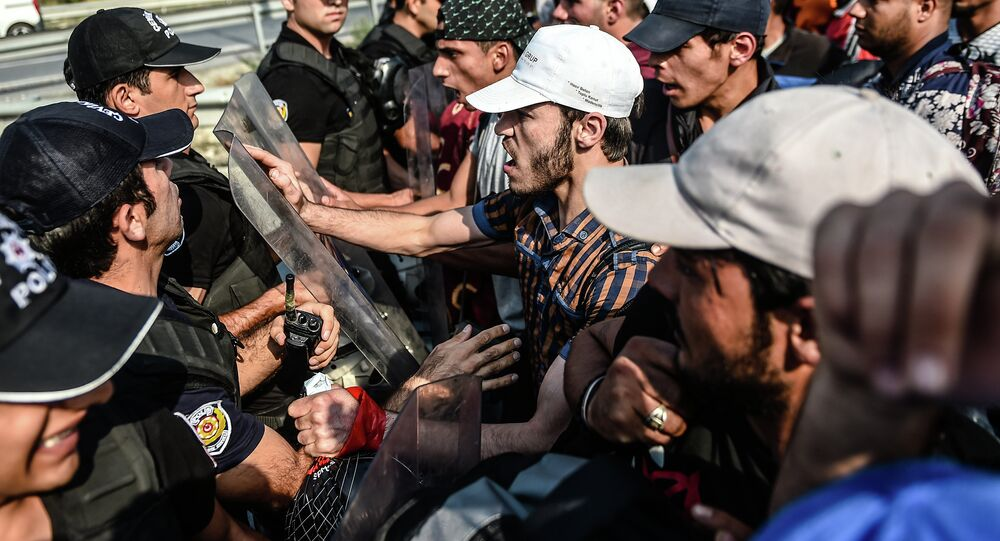 Migrants and refugees try to push a police barricade after they were blocked by Turkish riot police while walking towards Edirne on September 21, 2015 in Istanbul