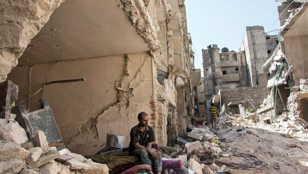 A Syrian man sits in the rubble following a barrel bomb attack the previous day on the rebel-held neighbourhood of al-Mashad in the northern Syrian city of Aleppo on September 17, 2015 - Sputnik International