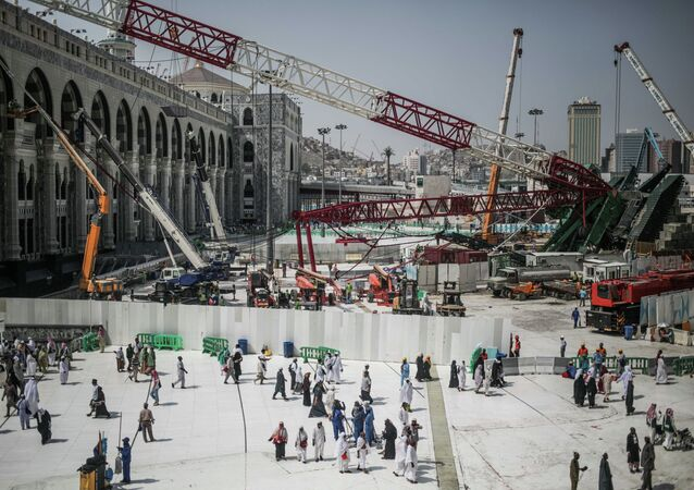 Muslim Pilgrims walk past the site of a crane collapse that killed over a hundred Friday at the Grand Mosque in the holy city of Mecca, Saudi Arabia, Tuesday, Sept. 15, 2015.
