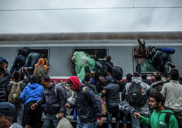 Migrants and refugees board a train by climbing through the windows as they try to avoid a police barrier at the station in Tovarnik, Croatia, Sunday, Sept. 20, 2015