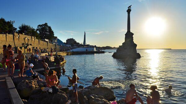 Holidaymakers and local residents bathe at dusk near a monument to sunken ships in Sevastopol - Sputnik International