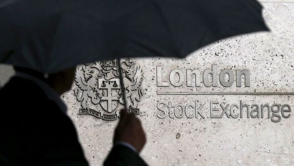 A man shelters under an umbrella as he walks past the London Stock Exchange in London, Britain, in this August 24, 2015 file photo - Sputnik International