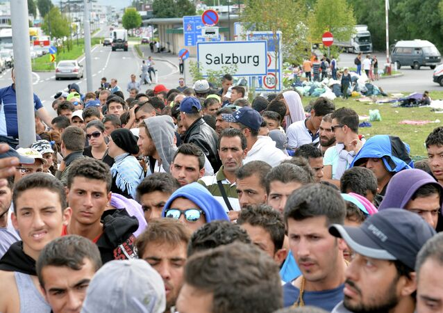 Refugees wait on a bridge after police stopped them at the border between Austria and Germany in Salzburg, Austria.
