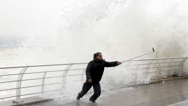 A man takes a selfie by a crashing wave on Beirut's Corniche, a seaside promenade, as high winds sweep through Lebanon during a storm in this February 11, 2015 file photo. - Sputnik International