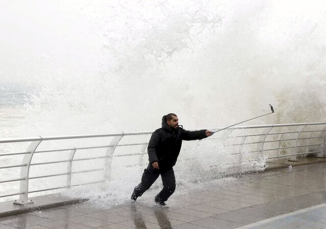 A man takes a selfie by a crashing wave on Beirut's Corniche, a seaside promenade, as high winds sweep through Lebanon during a storm in this February 11, 2015 file photo.