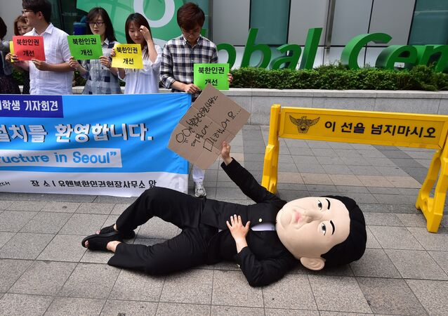 A South Korean activist wearing a mask depicting North Korean leader Kim Jong-Un lies on a street during a rally to welcome the opening of the UN Human Rights office at Seoul Global Center in Seoul on June 23, 2015