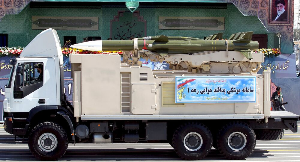 A military truck carrying a Raad missile drives past a picture of Iran's Supreme Leader Ayatollah Ali Khamenei (R) during a parade marking the anniversary of the Iran-Iraq war (1980-88), in Tehran