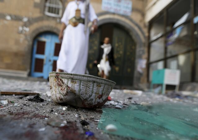 People walk past a headgear lying on the ground at the al-Balili mosque after two bombings at the mosque in Yemen's capital Sanaa September 24, 2015