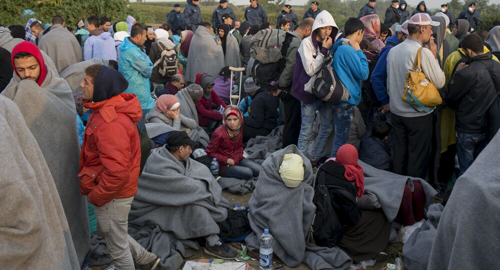 Migrants wait to board buses on a field, after they crossed the border with Serbia, near the village of Babska, Croatia September 24, 2015