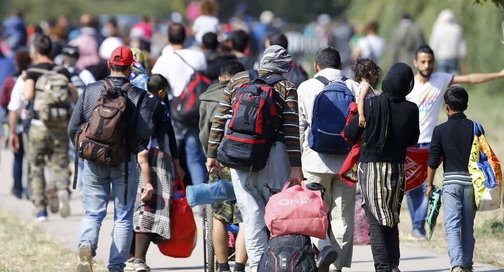 Migrants carry their belongings as they walk towards the Austrian border from Hegyeshalom, Hungary September 23, 2015.
